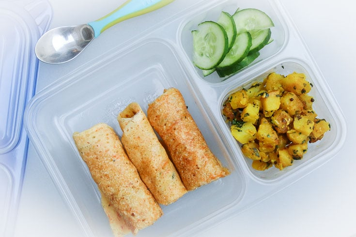 Overhead photograph of easy school lunch idea consisting of dosa, curried potatoes, and cucumbers.