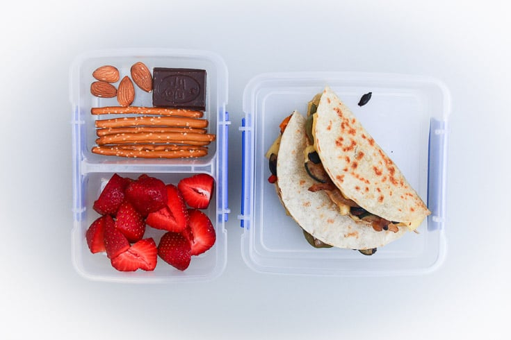 Overhead photograph of easy school lunch idea consisting of veggie quesadillas, strawberries, pretzels, almonds, and chocolate.