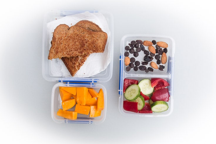 Overhead photograph of easy school lunch idea consisting of grilled cheese sandwich, fresh mango, trail mix, and raw veggies.