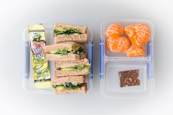 Overhead photograph of easy school lunch idea consisting of avocado spinach sandwiches, fruit wraps, oranges, and nut bar.