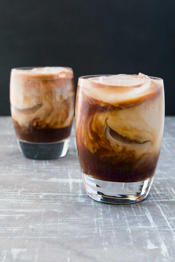Front photograph of two glass filled with aztec iced mocha recipe. The glasses are sitting on a gray board with black in the background.