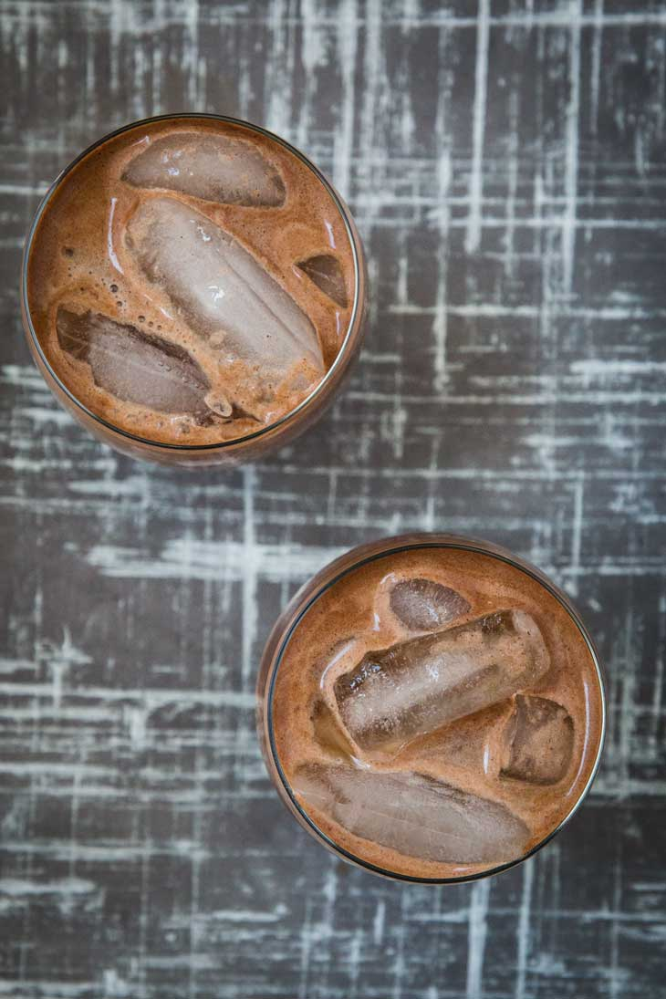 Overhead photograph of two glassed filled with an easy Aztec iced mocha recipe. They are sitting on a gray and white board.