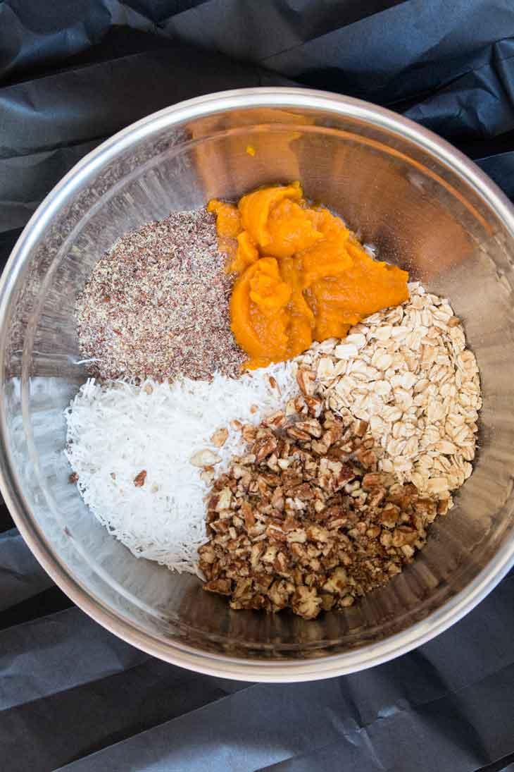 A mixing bowl containing the ingredients to make no-bake vegan pumpkin cookies. There's a steel bowl with flax seeds, coconut, pumpkin puree, pecans, and oats.