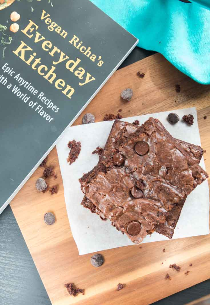 An overhead photograph of a stack of richa's vegan brownie recipe sitting next to 'vegan richa's everyday kitchen' cookbook.