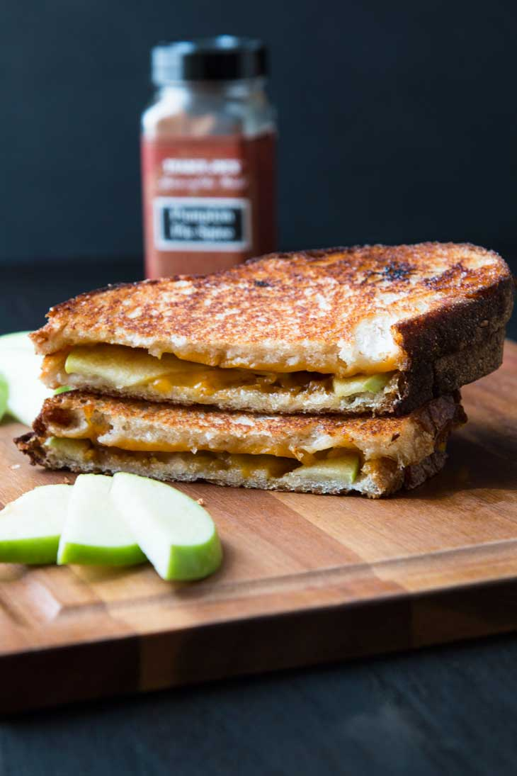 Pumpkin apple vegan grilled cheese cut in half and stalked on top of a brown cutting board with green apples off to the side.