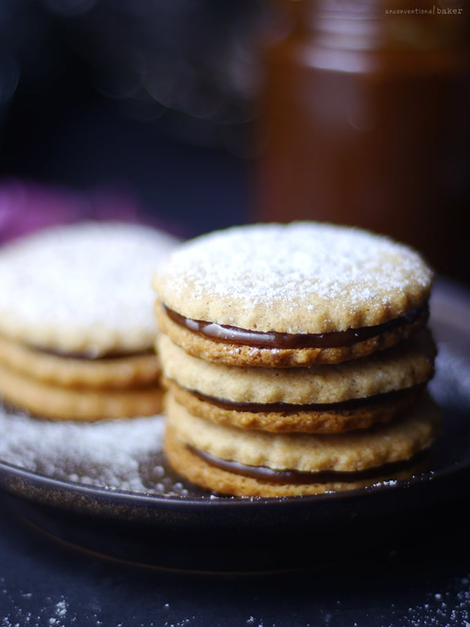 A stack of caramel sandwich cookies dusted with powdered sugar.