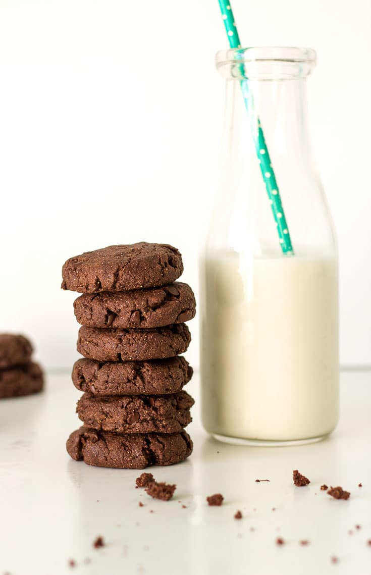 A stack of chocolate cookies sitting next to a jug of milk containing a green straw.