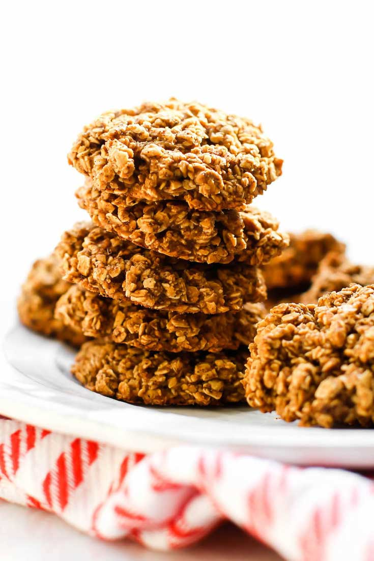 Chunky vegan gingersnap oatmeal cookies stacked and sitting on a white plate. There's a red and white town under the plate.