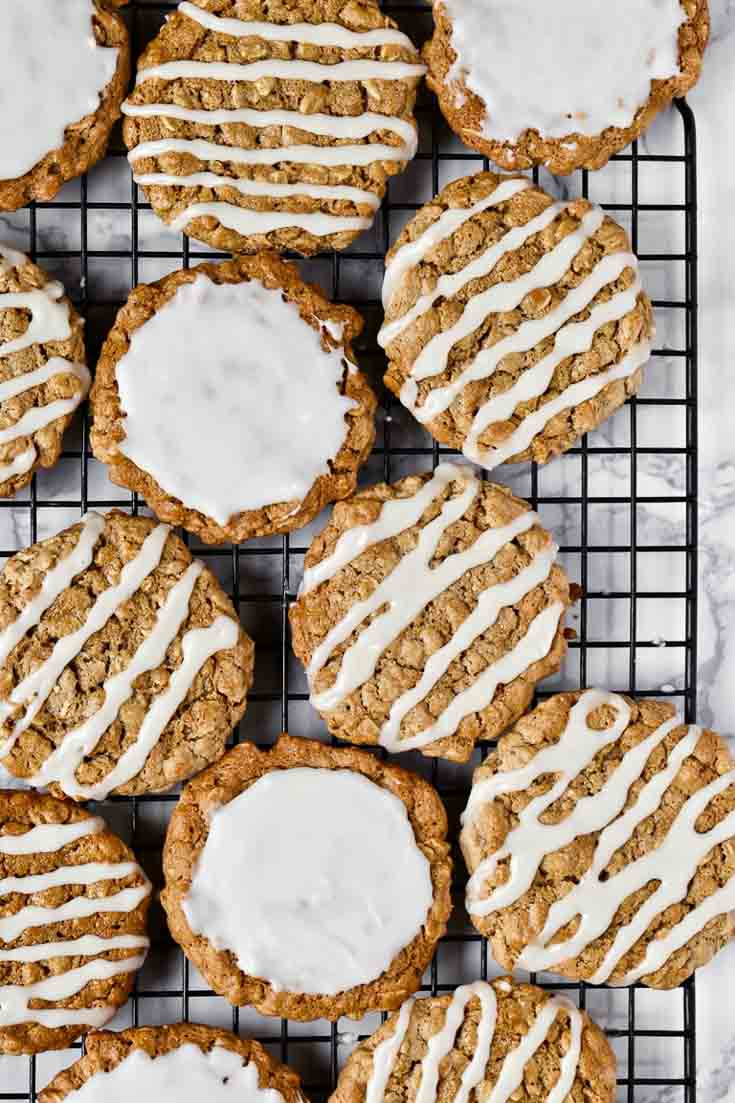 Overhead photograph of old fashion glazed oatmeal cookies sitting on a cookie cooling rack.