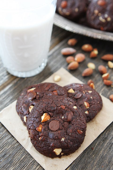 Vegan chocolate almond cookies sitting on some parchment paper next to some raw almonds and a glass of milk.