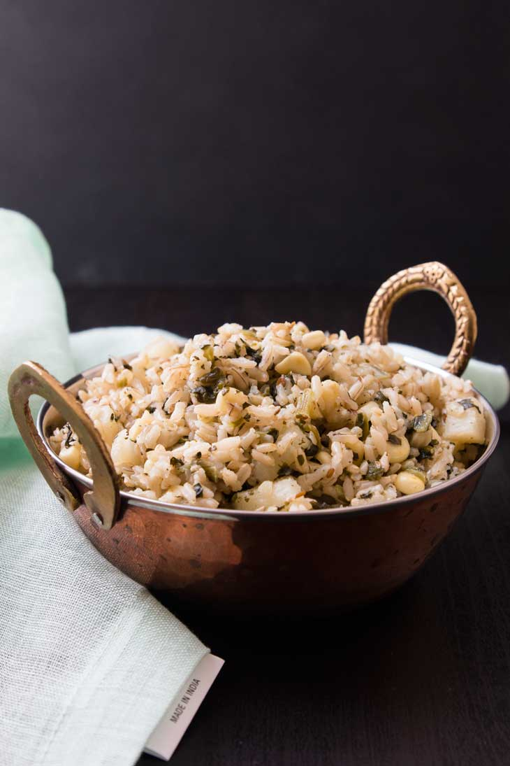 A side view of vegetable pulau rice recipe served in a copper bowl with a light green napkin sitting on the side.