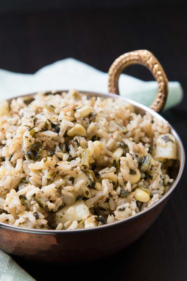Quick indian pulao rice recipe with potatoes, spinach, and corn in a copper serving bowl.