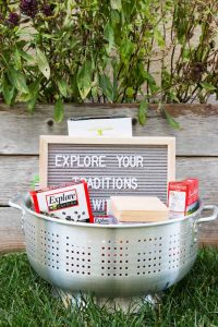 A huge colander containing explore cuisine pasta boxes and a sign sitting on the grass.
