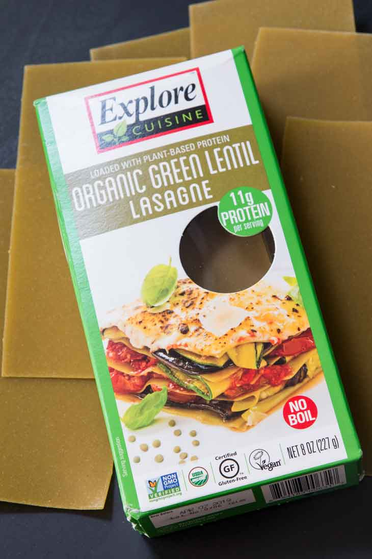 A box of explore cusine green lentil lasagna sheets with some sheets laying under.