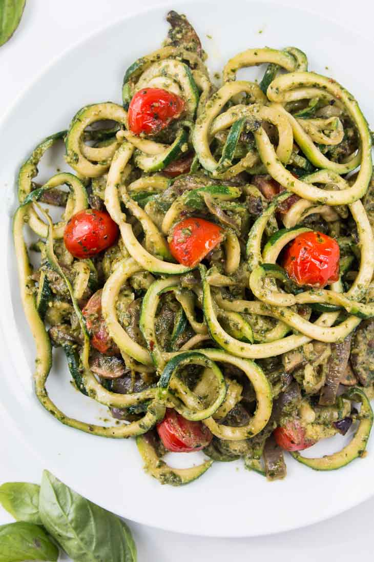 Fourth best vegan meal on VG in 2017. Overhead photograph of spiralized zucchini noodles with pesto and cherry tomatoes plated on a round white plate.