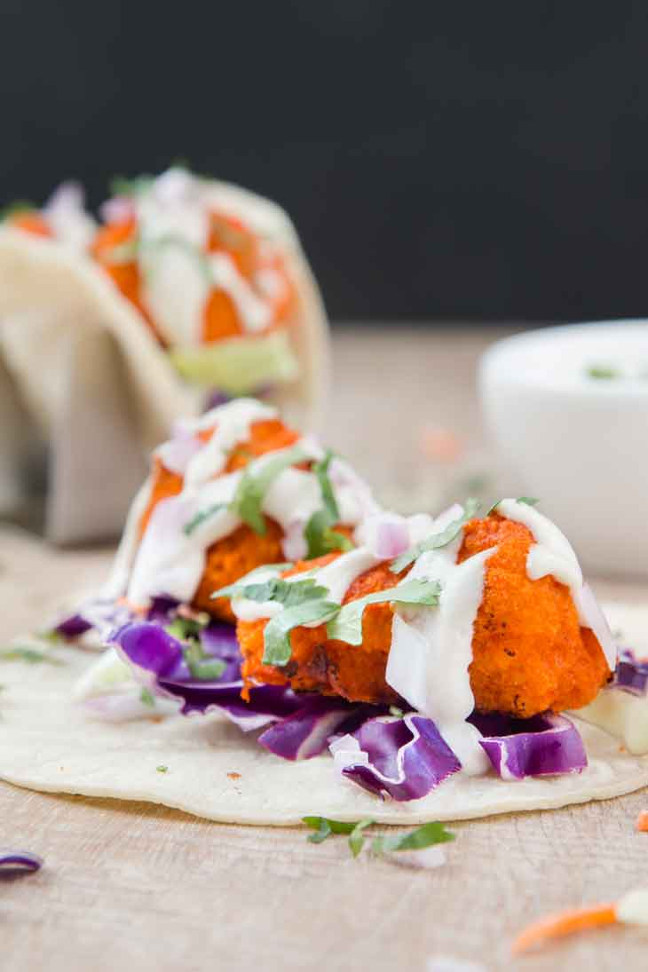 Third best vegan meal on VG in 2017. Vegan Buffalo Cauliflower Tacos with slaw and topped with ranch, sitting on a wooden board.