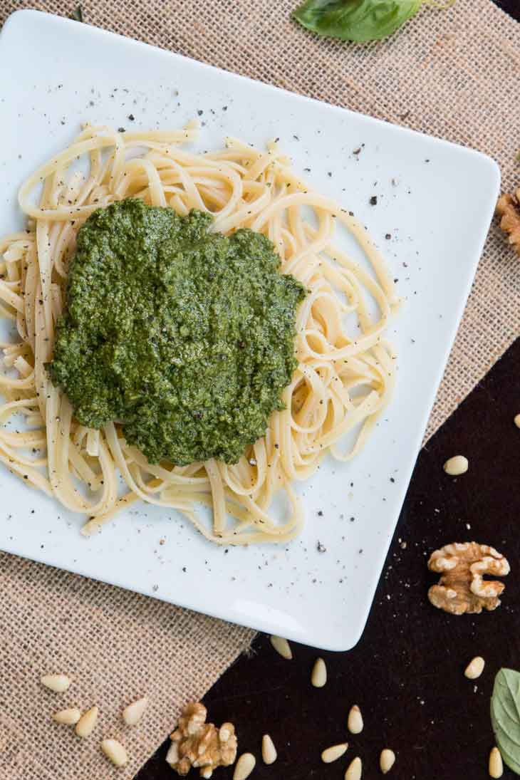 Fifth best vegan meal on VG in 2017. An overhead photograph of linguine pasta topped with vegan pesto, all plated on a square white plate. The table is garnished with nuts and basil.