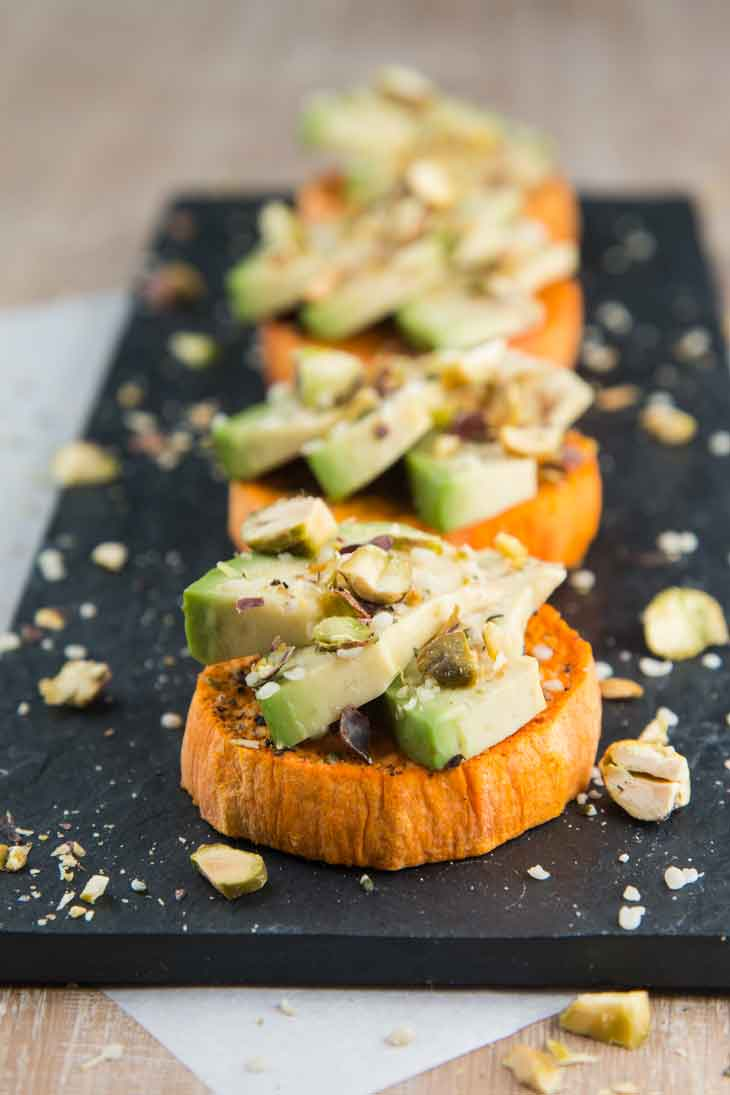 Best vegan meal on VG in 2017. Four sweet potato avocado toasts topped with pistachios and hemp seeds sitting on a black rectangular palate.