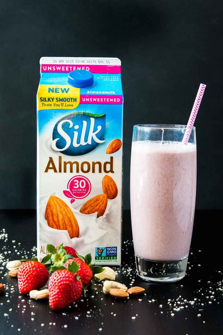 A photograph of a tall glass filled with nutty strawberry date milk and a pink straw. The glass is sitting next to a half gallon of silk almondmilk container. THere are strawberries, nuts, and hemp seeds scattered around.