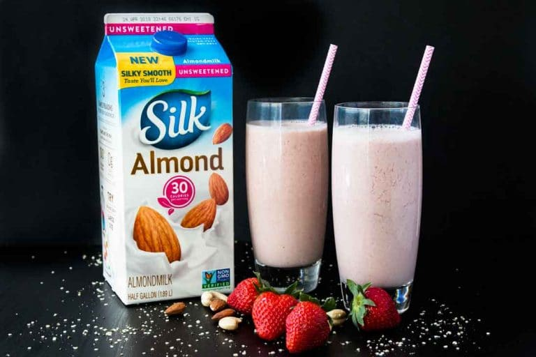 A side photograph of two tall glasses filled with strawberry date milk, containing pink straws. There's a container of silk almond milk, and strawberries, hemp seeds, and nuts scattered around.