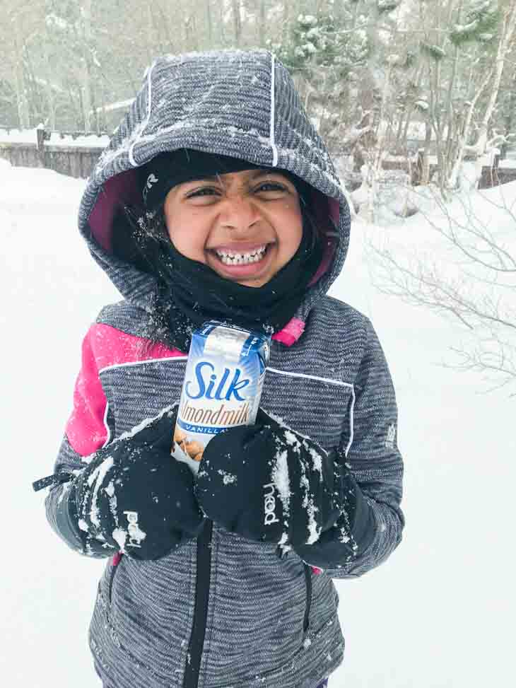 A child holding silk almondmilk single serving in the snow.