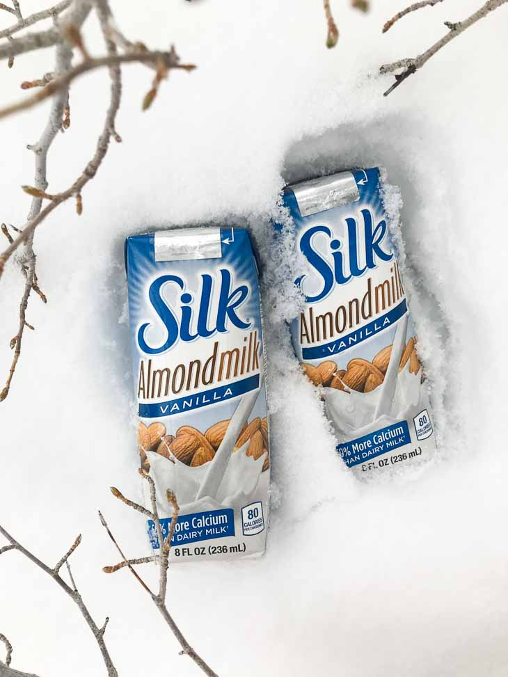 Two single serving silk almond milk containers sitting in the snow with branches on the side.