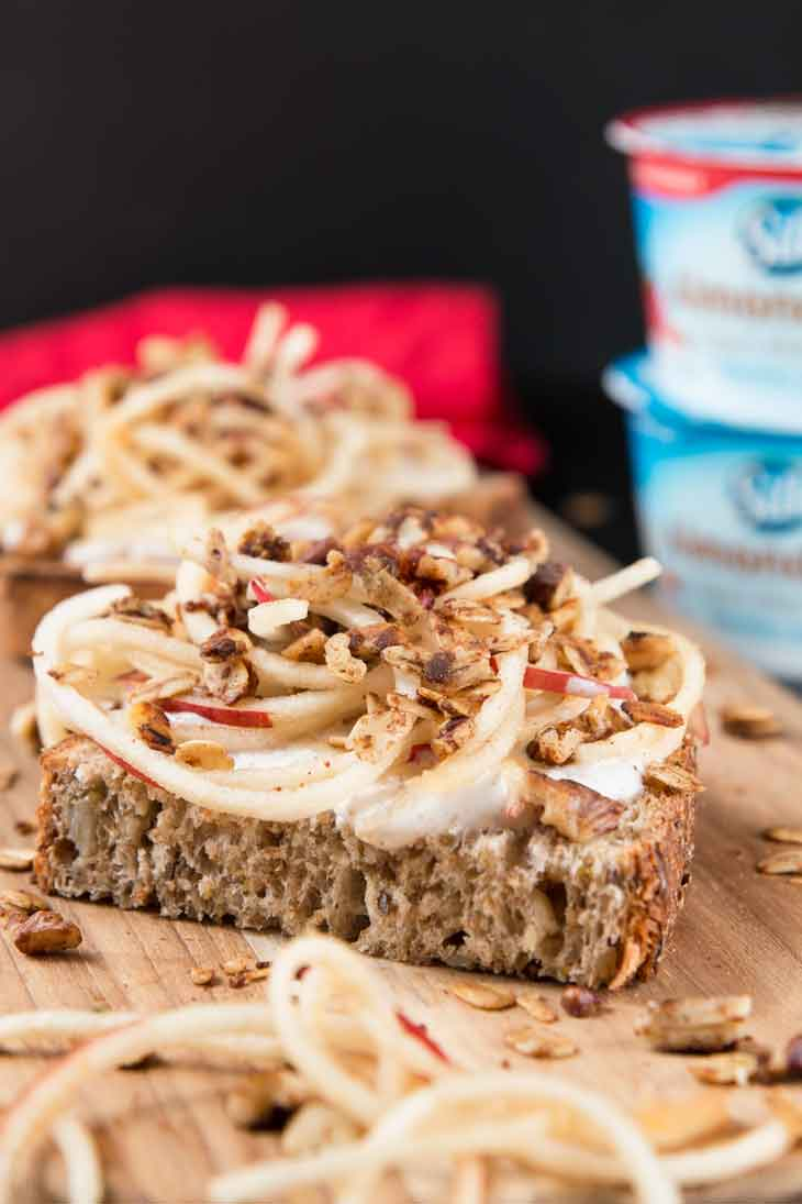 A close-up side photograph of vanilla yogurt cinnamon toast recipe on a cutting board with spiralized apples and granola. A red napkin and stalked almondmilk yogurt cups are in the background.