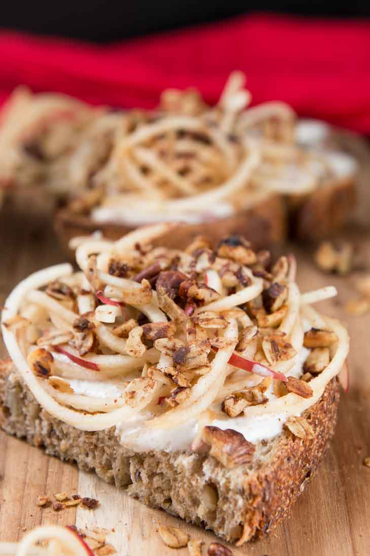 Photograph of vanilla yogurt cinnamon toast recipe topped with spiralized apples and granola. There's a red napkin in the background.