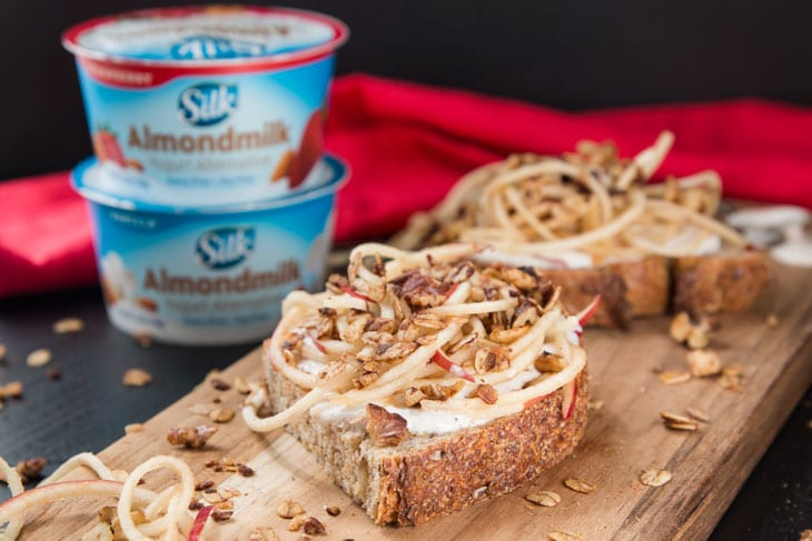 A side photograph of vanilla yogurt cinnamon toast recipe on a cutting board with spiralized apples and granola sprinkled on and around. There are two stacked single-serving SILK almondmilk yogurt cups in the background.