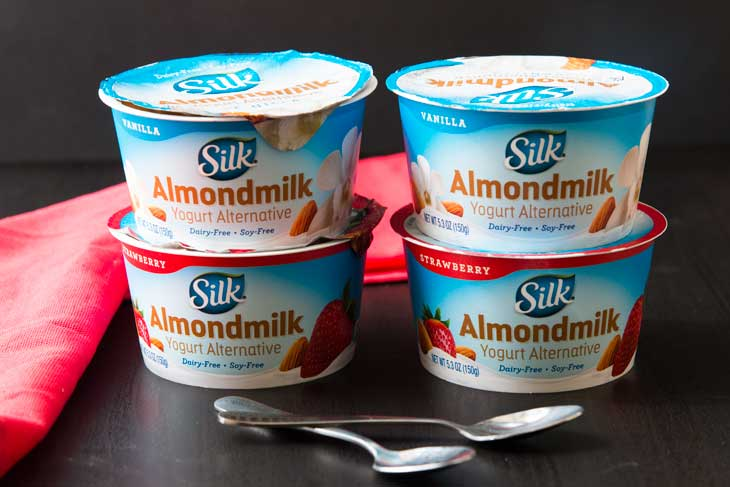 Photograph of 4 different single-serving SILK almond milk yogurt alternative cups. There are two spoons in front and a red napkin in the background.