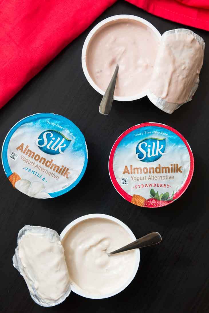 An overhead photograph of 4 single-serving SILK almondmilk yogurt . Two of the servings are open with spoons inside.