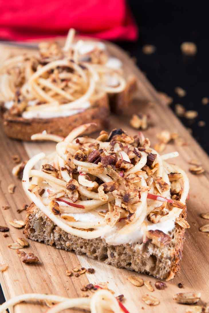 A 45 degree photograph of vanilla yogurt cinnamon toast recipe topped with spiralized apples and granola, served on a cutting board. There's a red napkin in the background.