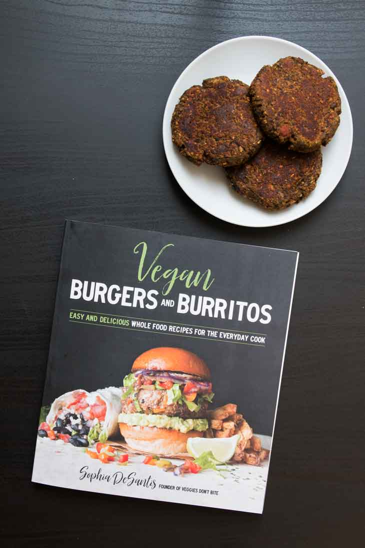 An overhead photograph of the vegan burgers & burritos cookbook. There's a side plate with patties of a vegan burger recipe out of the cookbook.