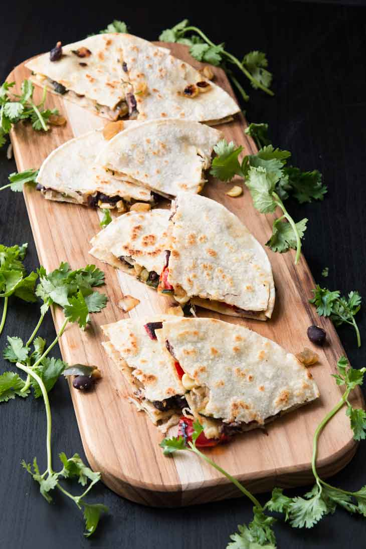 Overhead photograph of grilled veggie quesadilla cut into quarters and spread on a cutting board with fresh cilantro.