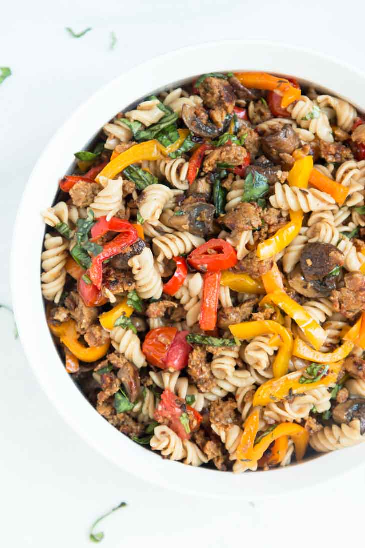 Overhead photograph of vegan pasta salad with italian sausage, mushrooms, peppers, basil, & cherry tomatoes.