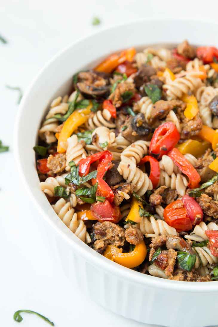 A closeup side photograph of vegan pasta salad with italian sausage, mushrooms, peppers, and cherry tomatoes.