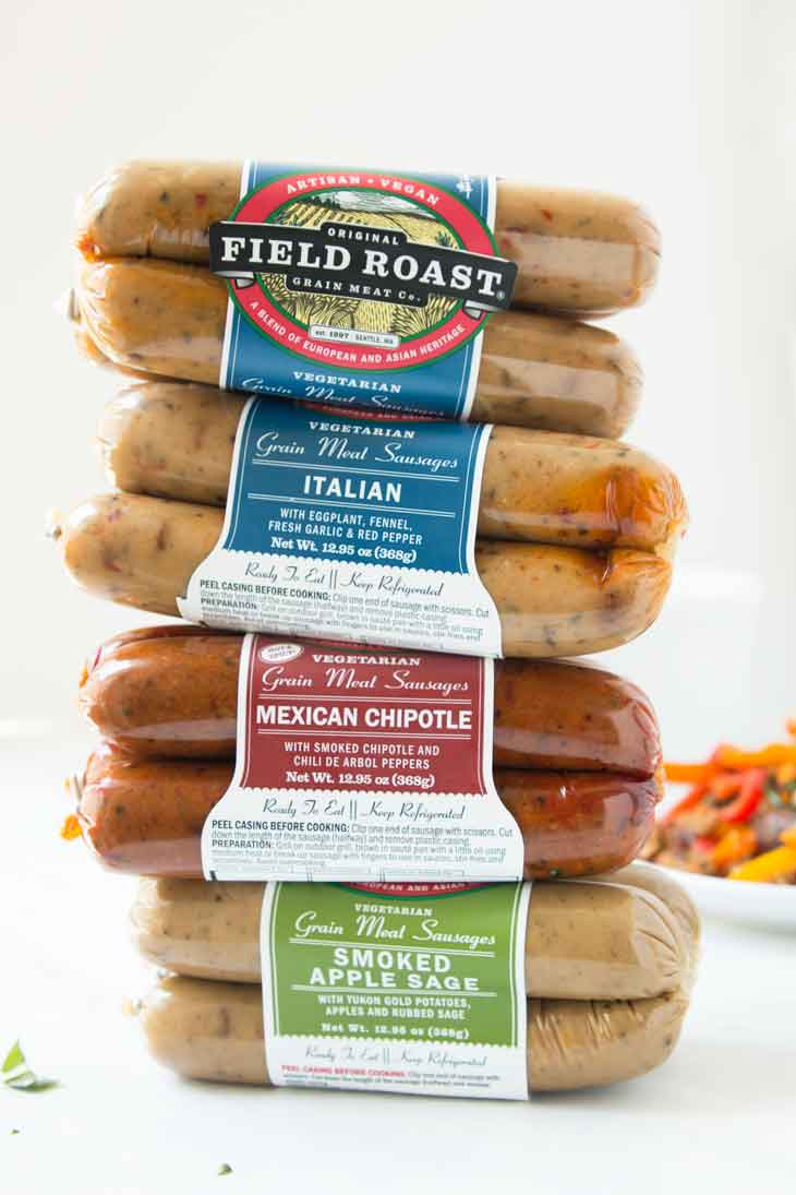 A stack of field roast vegan italian sausages on display in front of some vegan pasta salad.