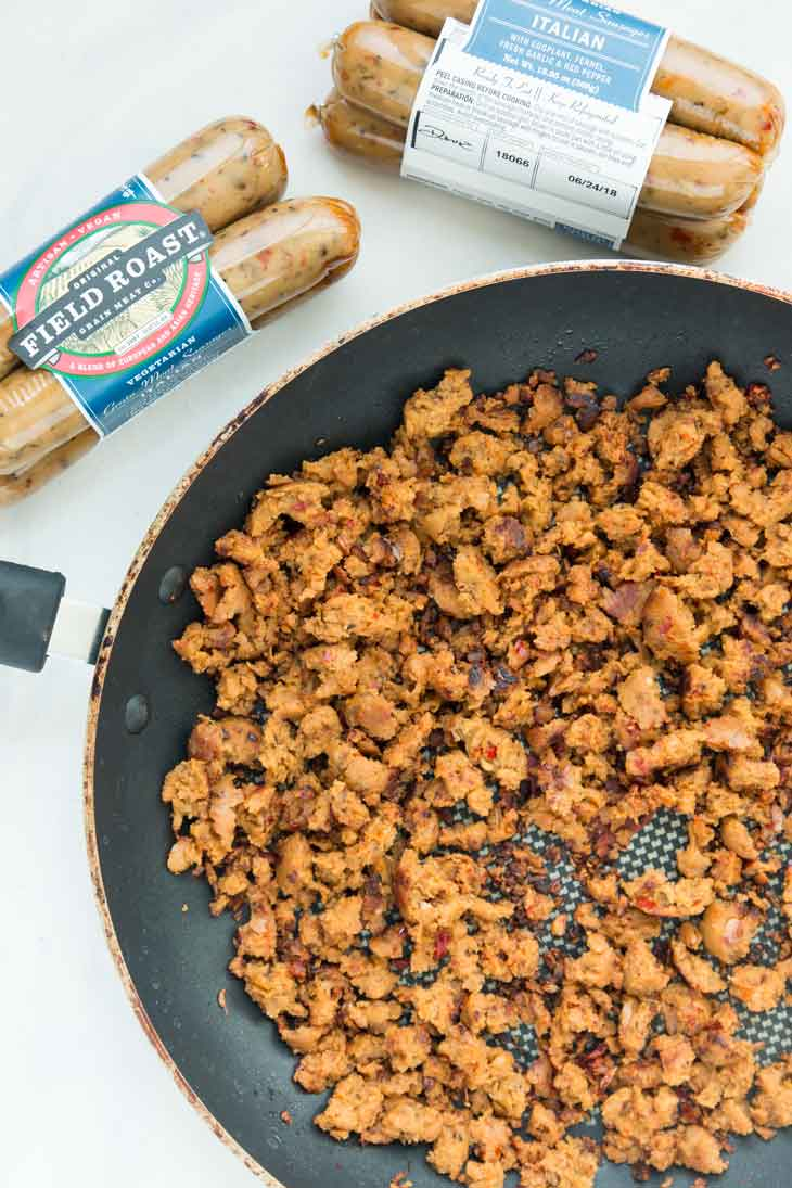 Field roast vegan italian sausage crumbled and sauteed in a pan, ready to be added to a vegan pasta salad.