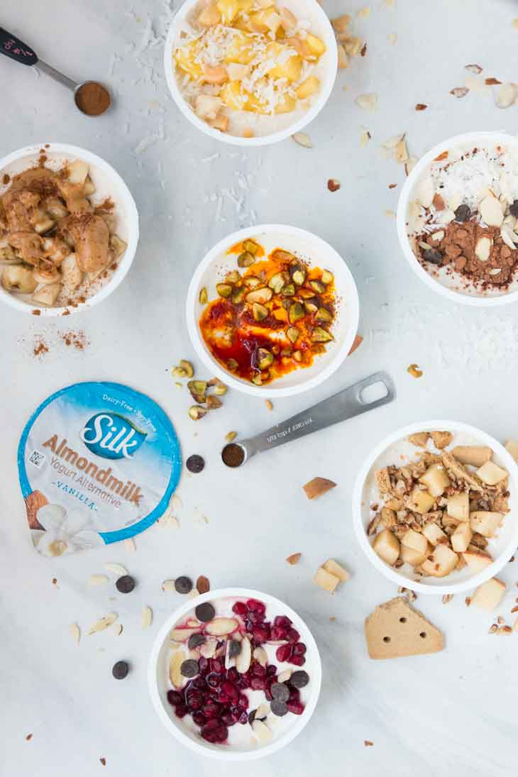 Overhead photograph of 6 healthy yogurt cup combinations.