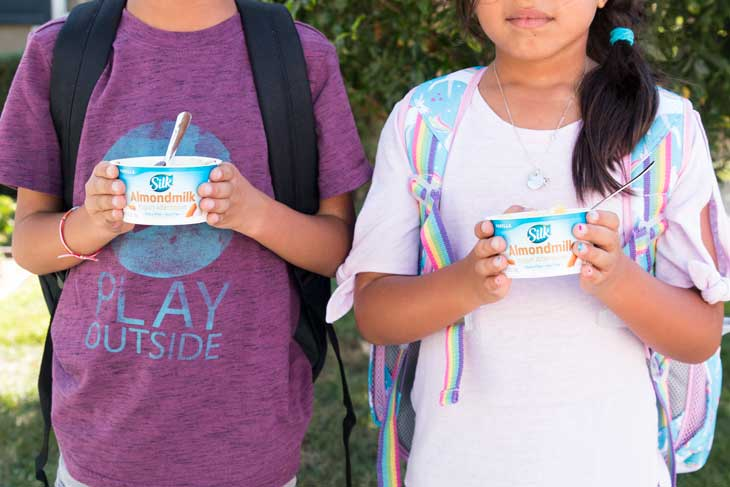 A front photograph of two kids enjoying vegan healthy yogurt cups.