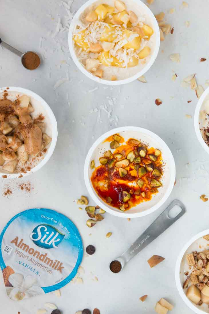 Overhead closeup of healthy yogurt cup combinations with ingredients scattered around.