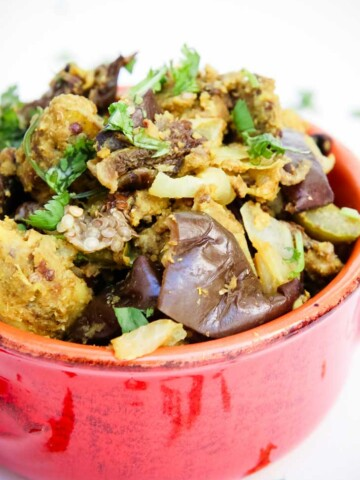 Indian stuffed baked eggplant and potatoes in a large red bowl