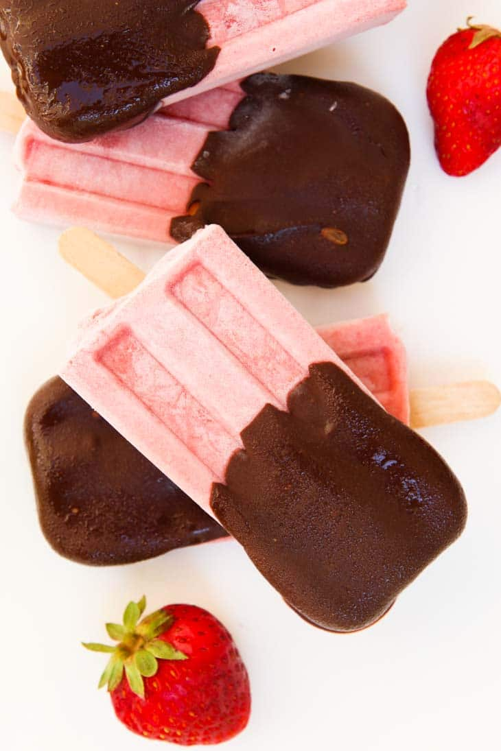 An overhead shot of strawberry Popsicle covered with chocolate