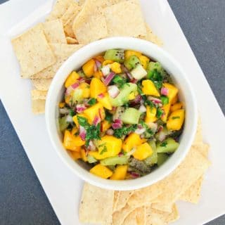 A mango and kiwi fruit salsa in a white bowl with tortillas chips