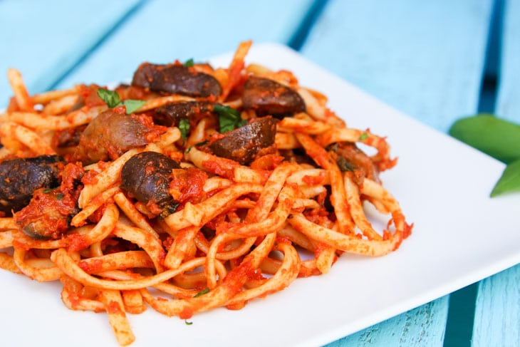 A close up of linguine with roasted mushrooms with a tomato sauce