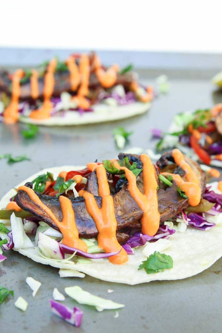 Portobello mushrooms tacos topped with vegetables and spicy sauce