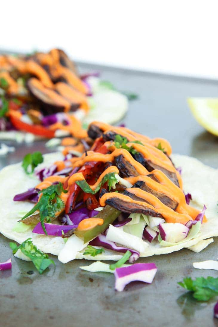 A close up of a mushroom tacos topped with a bright orange spicy sauce