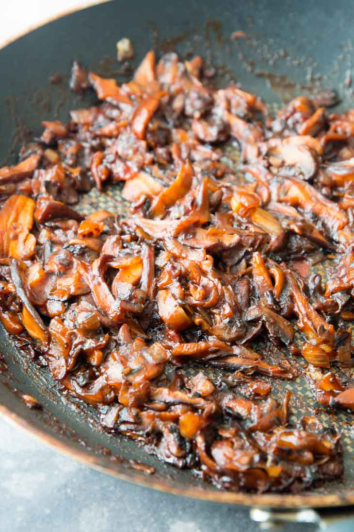 A thick and sticky bbq sauce and mushroom mixture cooking on a pan, for a bbq sandwich recipe.