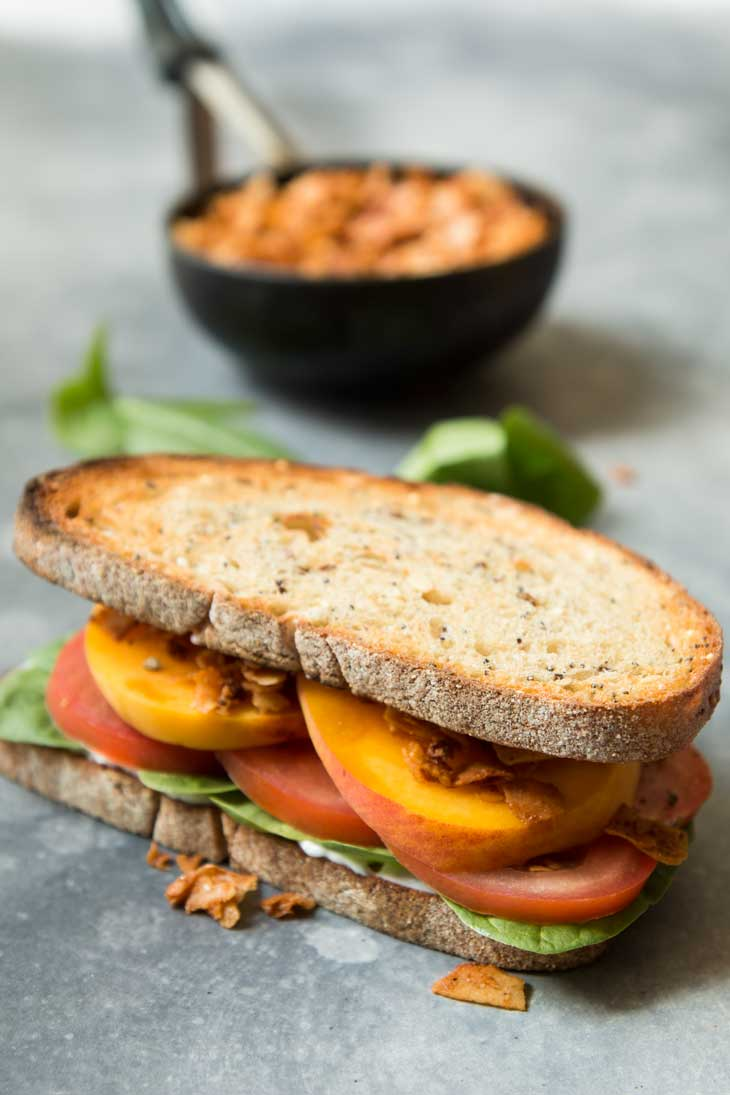 Side photoraph of vegan BLT sandwich with spinach, peaches, and coconut bacon. There's coconut bacon in the background.