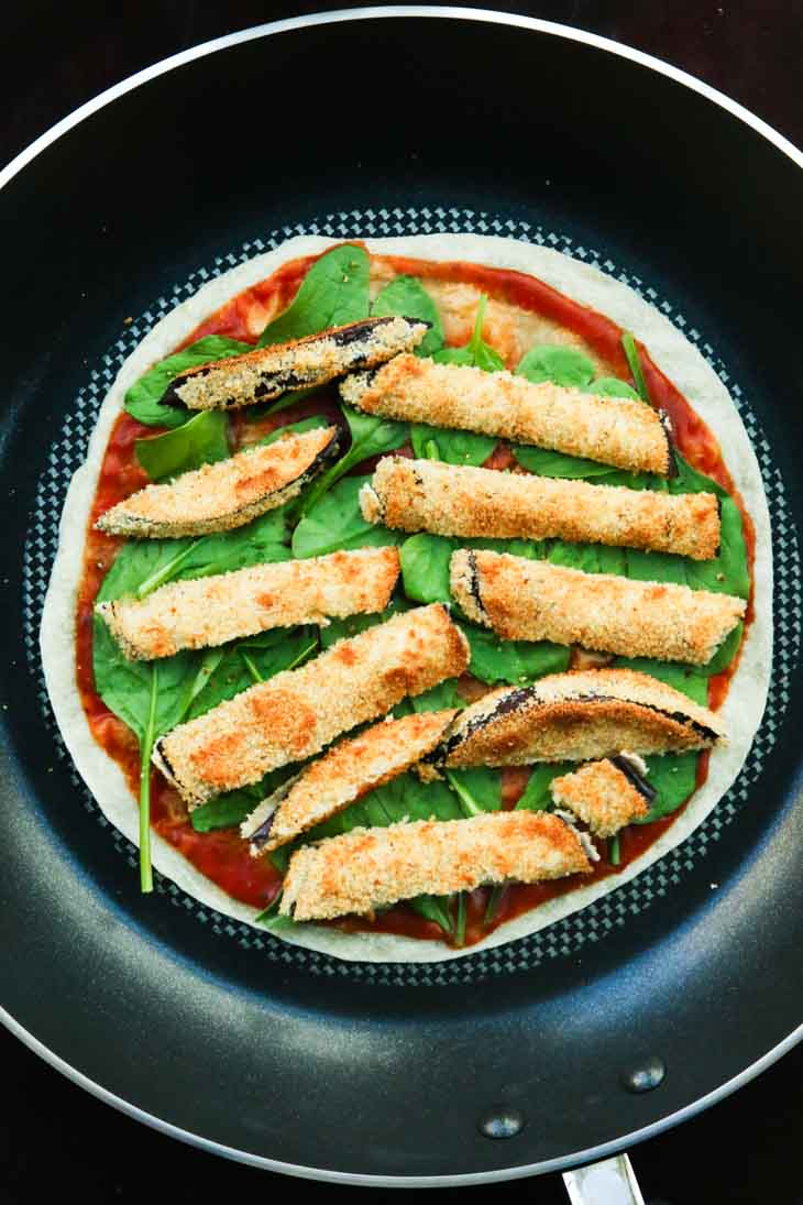 A tortilla with crispy grilled eggplant spinach and tomato sauce in a pan